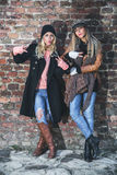 Girlfriends showing peace signs. Girlfriends leaning on the brick wall and showing peace signs Royalty Free Stock Photo