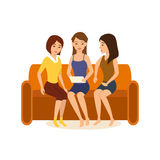 Girlfriends are sitting on couch, discussing photos and funny stories. Girlfriends are sitting at home on the couch, holding a tablet in hand and discussing Royalty Free Stock Image