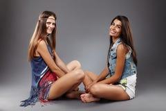 Girlfriends sitting cross legged Stock Photos