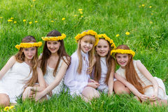 Girlfriends are sitting in the grass with wreaths of dandelions. On their heads in the open air. Five beautiful young girls in white dresses in summer park Stock Photo