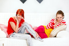 Girlfriends sitting on sofa and talking on mobiles Stock Photos