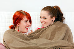 Girlfriends sitting on sofa wrapped up in plaid Royalty Free Stock Photo