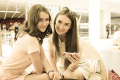Girlfriends with smartphone in shopping mall Stock Photo