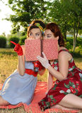 Girlfriends spying. Two spy girl hiding face behind the book retro Stock Images