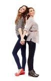 Girlfriends standing back to back and holding hands Stock Photos