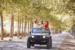 Girlfriends standing up in the back of an open top jeep royalty free stock photo