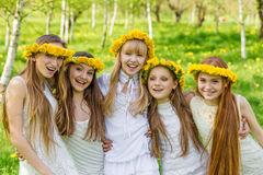 Girlfriends are standing with wreaths of dandelions on their hea Royalty Free Stock Photos