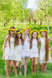 Girlfriends are standing with wreaths of dandelions on their heads in the open air royalty free stock photos