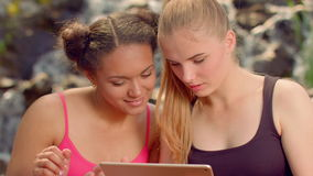 Girlfriends surfing internet on tablet computer outdoors. Closeup of multiracial friends reading news on tablet together. Two girls read tablet. Multiracial stock video
