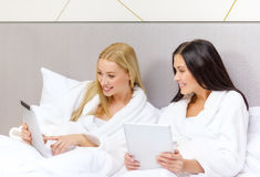 Girlfriends with tablet pc computers in bed Royalty Free Stock Photos