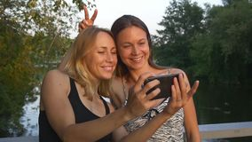 Girlfriends taking selfie in the park. Young women taking selfie on the phone outdoor in the park near lake stock footage