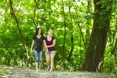 Girlfriends taking a walk through the park, horizontal Royalty Free Stock Photos