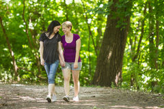 Girlfriends taking a walk through the park, horizontal Stock Images