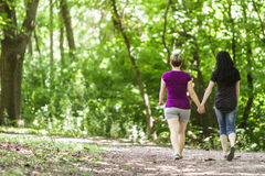 Girlfriends taking a walk through the park, horizontal Royalty Free Stock Photo