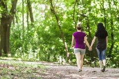 Girlfriends taking a walk through the park, horizontal Royalty Free Stock Photo