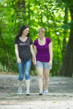 Girlfriends taking a walk through the park, vertical Stock Images