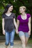 Girlfriends taking a walk through the park, vertical Royalty Free Stock Photos