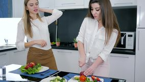 Girlfriends talk on kitchen and prepare salad at the table, girl slicing apple on a cutting board. Girlfriends talk on kitchen and prepare a salad at the table stock video