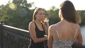 Girlfriends talking on a bridge. Two young ladies chatting in the park standing on a bridge across the river at sunset stock video footage
