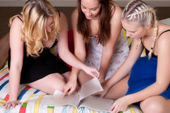 Girlfriends talking about a magazine on bed Royalty Free Stock Photos