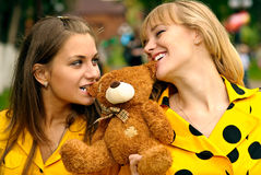 Girlfriends with toy bear cub Stock Images