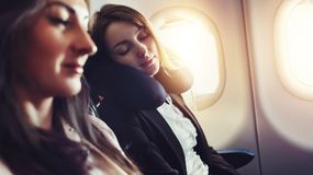 Girlfriends traveling by plane. A female passenger sleeping on neck cushion in airplane. Girlfriends traveling by plane. A female passenger sleeping on neck royalty free stock image