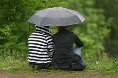 Girlfriends under a umbrella Stock Image