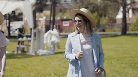 Girlfriends walk and spend time together in the park. Two woman in hat. Three beautiful young women in sunglasses embrace, have fun and are photographed against stock footage