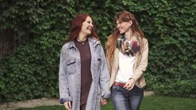 Girlfriends are walking around the city and holding hands. Best friends together. 20s. Red-haired girlfriends are walking in the park and holding hands stock video footage