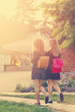 Girlfriends walking through park. Royalty Free Stock Images