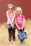 Girlfriends in windy grassy field. Two silly little elementary aged girls playing and dancing in a windy grassy field. Shallow depth of field Royalty Free Stock Photos