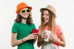 Girlfriends 12-14 years old, on white background in hats talking, holding cups Royalty Free Stock Photo