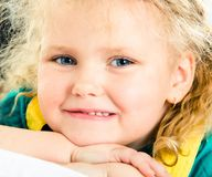 Girlie. Face of pretty little girl looking at camera with smile with her chin on hands stock image