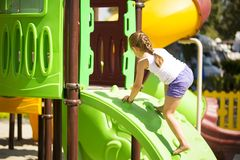 Girlie climbing on jungle gym. Little caucasian girlie climbing on jungle gym, sunny summer day,recreation concept stock photos