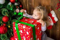 Girlie feliz hermoso abre el regalo del ` s del Año Nuevo fotos de archivo libres de regalías