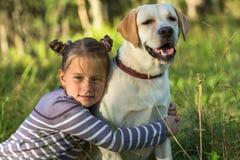 Girlie hugging her dog outdoors. Summer. Royalty Free Stock Images