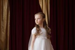 Girlie i den vita klänningen som poserar på gardinbakgrunden royaltyfria foton