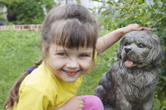 Girlie near to concrete dog. Girlie smiling near to concrete dog in garden royalty free stock photography