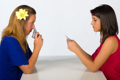 Girlie poker. Blond and brunette in a serious poker confrontation royalty free stock photography