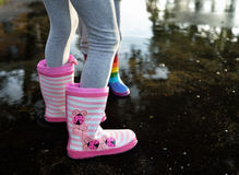 Girlie striped wellingtons in the puddle. Playing kids wearing striped wellingtons in the puddle stock images