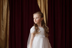 Girlie in white dress posing on curtain backdrop Royalty Free Stock Photos