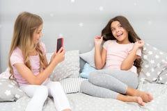 Girlish партия пижамы отдыха Smartphone девушек представляя большую съемку Пошлите фото социальную сеть используя smartphone Smar стоковое фото rf
