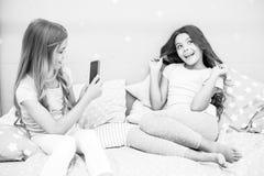 Girlish партия пижамы отдыха Smartphone девушек представляя большую съемку Пошлите фото социальную сеть используя smartphone Smar стоковые изображения