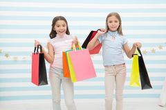 Girlish happiness. Kids happy carry bunch packages. Shopping with best friend concept. Girls like shopping. Kids happy. Small girls hold shopping bags. Enjoy stock photos