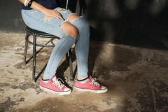 Girlish legs in torn jeans Royalty Free Stock Photos