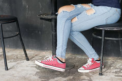 Girlish legs in torn jeans Royalty Free Stock Images