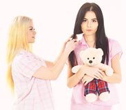 Girlish leisure concept. Sisters, best friends in pajamas making braid, hairdo each other. Ladies on smiling faces with. Plush toy bear look cute. Girls in pink royalty free stock images