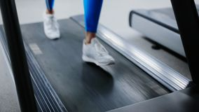 Feet run along the treadmill close up. Girlish running on the treadmill in the gym stock video footage
