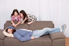 Girlish team. Family prank. Mom and daughter going to cut beard sleeping dad. Lets have fun. Cheerful girls with stock image
