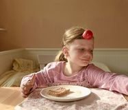 Girll ребенк ест сливк шоколада распространенную на хлебе Закуска еды шоколада сладостная Счастливая девушка имеет закуску в кухн Стоковые Изображения RF